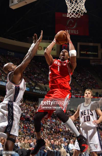 Tracy McGrady of the Houston Rockets shoots against Marc Jackson of the New Jersey Nets at the Continental Airlines Arena on November 12 2005 in East...