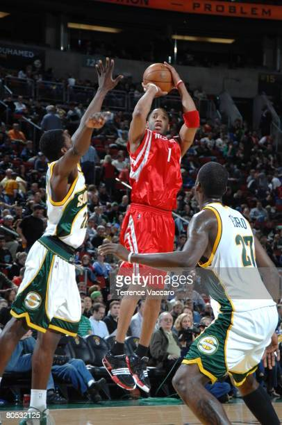 Tracy McGrady of the Houston Rockets shoots over the defense of Jeff Green and Johan Petro of the Seattle SuperSonics on April 4 2008 at the Key...