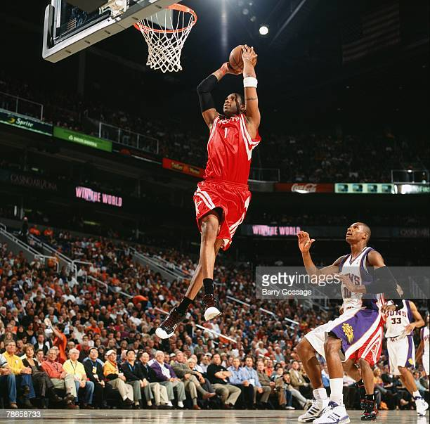 Tracy McGrady of the Houston Rockets takes the ball to the basket for a dunk past Leandro Barbosa of the Phoenix Suns during the game at US Airways...