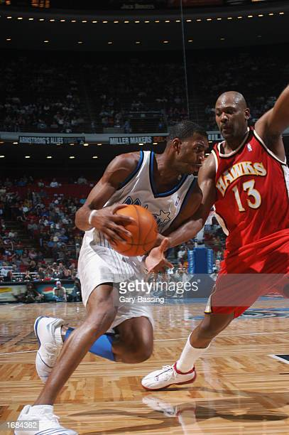Tracy McGrady of the Orlando Magic drives to the basket against Glenn Robinson of the Atlanta Hawks during the NBA game at TD Waterhouse Centre on...
