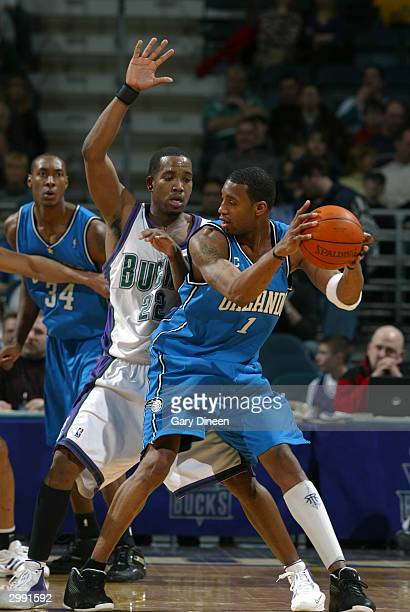 Tracy McGrady of the Orlando Magic looks to pass around Michael Redd of the Milwaukee Bucks February 17 2004 at the Bradley Center in Milwaukee...