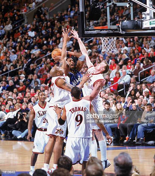 Tracy McGrady of the Orlando Magic makes a jump shot over Derrick Coleman and Keith Van Horn of the Philadelphia 76ers at First Union Center on...