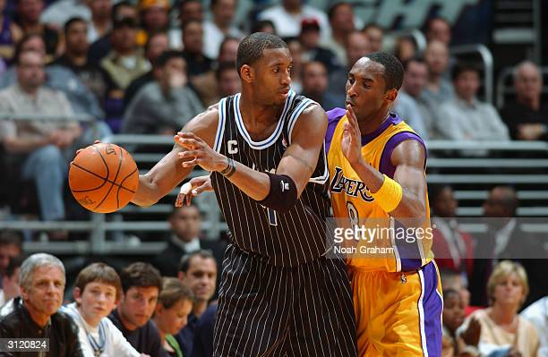 Tracy McGrady of the Orlando Magic posts up Kobe Bryant of the Los Angeles Lakers during the game at the Staples Center on March 15, 2004 in Los...