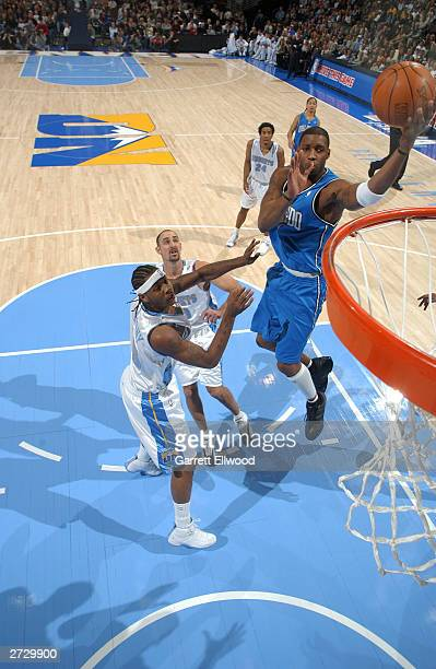 Tracy McGrady of the Orlando Magic shoots against Carmelo Anthony of the Denver Nuggets November 14 2003 at the Pepsi Center in Denver Colorado NOTE...