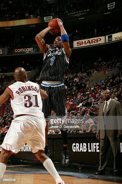 Tracy McGrady of the Orlando Magic shoots against Glenn Robinson of the Philadelphia 76ers January 23 2004 at the Wachovia Center in Philadelphia...