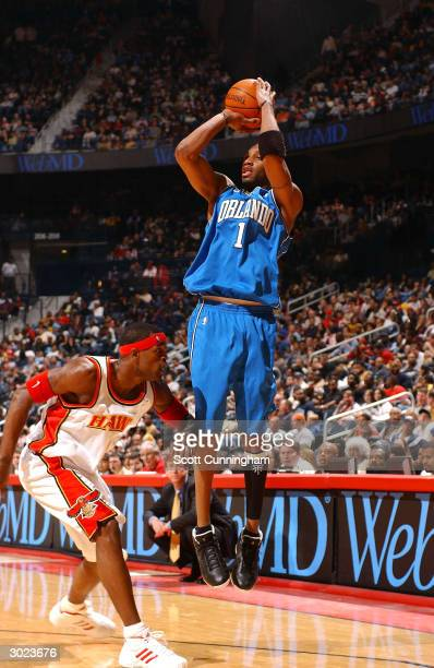 Tracy McGrady of the Orlando Magic shoots against Stephen Jackson of the Atlanta Hawks on February 28 2004 at Philips Arena in Atlanta Georgia NOTE...