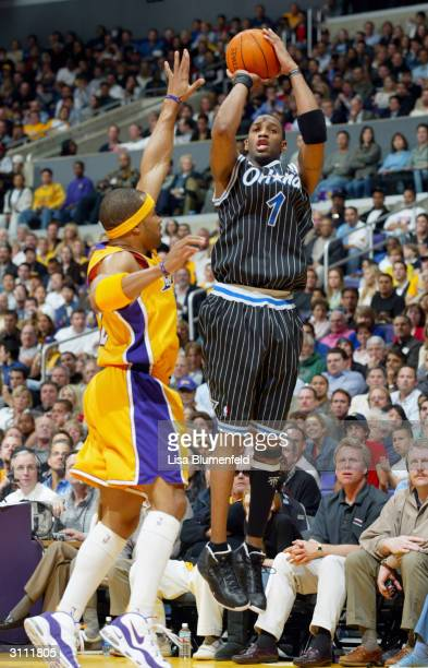 Tracy McGrady of the Orlando Magic shoots over Derek Fisher of the Los Angeles Lakers during the game at Staples Center on March 15, 2004 in Los...