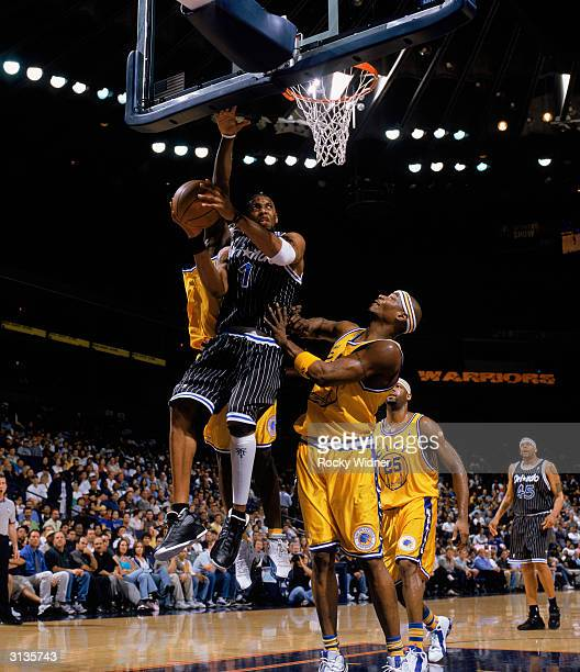 Tracy McGrady of the Orlando Magic takes the ball up against Clifford Robinson#3 of the Golden State Warriors during the NBA game at The Arena in...