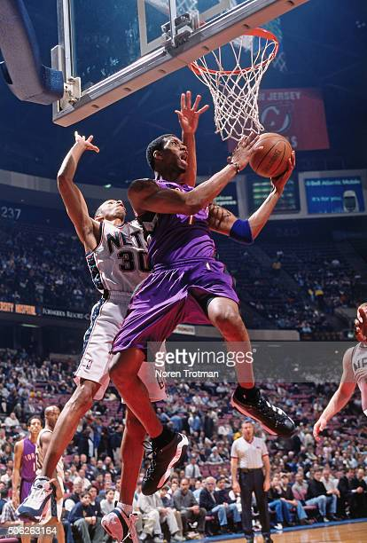 Tracy McGrady of the Toronto Raptors shoots against Kerry Kittles of the New Jersey Nets on March 30 2000 at Continental Airlines Arena in East...