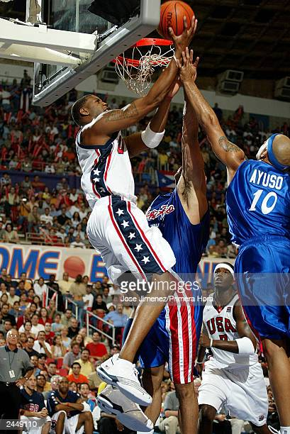 Tracy McGrady of the U.S. Drives in front of Larry Ayuso and Jose Ortiz of Puerto Rico during the U.S. Versus Puerto Rico semifinal Olympic...