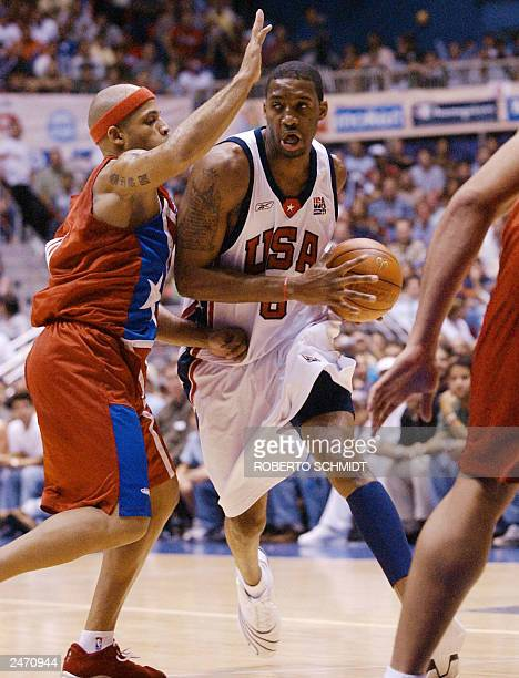 Tracy McGrady of the US drives to the basket past Elias Ayuso of Puerto Rico during their second round game at the Roberto Clemente Coliseum in San...