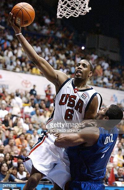 Tracy McGrady of the US goes to the basket to score two points over Jose Ortiz of Puerto Rico in their semi-final game at the Roberto Clemente...