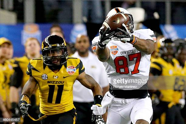Tracy Moore of the Oklahoma State Cowboys makes a 41-yard catch against Aarion Penton of the Missouri Tigers in the fourth quarter during the AT&T...
