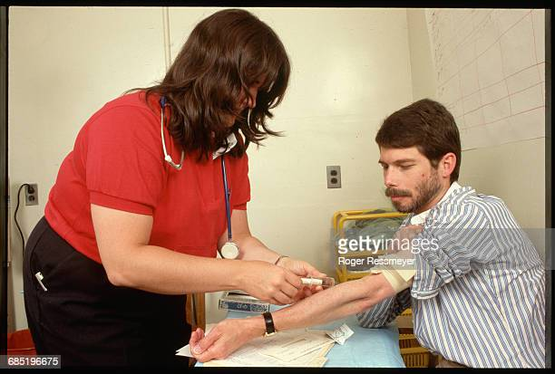 Tracy Moran, Oncology Nurse at San Francisco General Hospital, takes a blood sample from George W. Riley, a patient with AIDS.