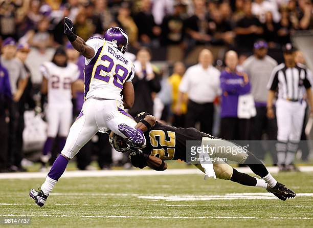 Tracy Porter of the New Orleans Saints attempts to tackle Adrian Peterson of the Minnesota Vikings during the NFC Championship Game at the Louisana...