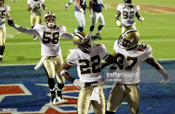 Tracy Porter of the New Orleans Saints celebrates with teammates Malcolm Jenkins and Scott Shanle after retuning a interception for touchdown against...
