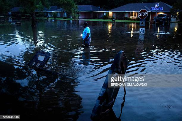 Tracy Thornton walks to his house through a flooded neighborhood August 15, 2016 in Baton Rouge, Louisiana. Floods ravaged the US state of Louisiana,...