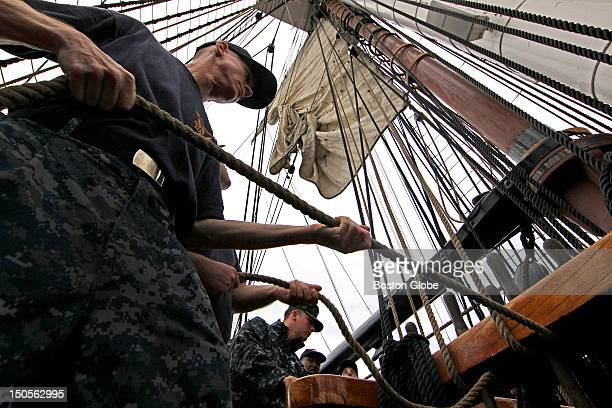 Tracy Walker Chief Petty Officer Select of the US Navy left helps to hoist a sail with crew members of the USS Constitution and Chief Petty Officers...