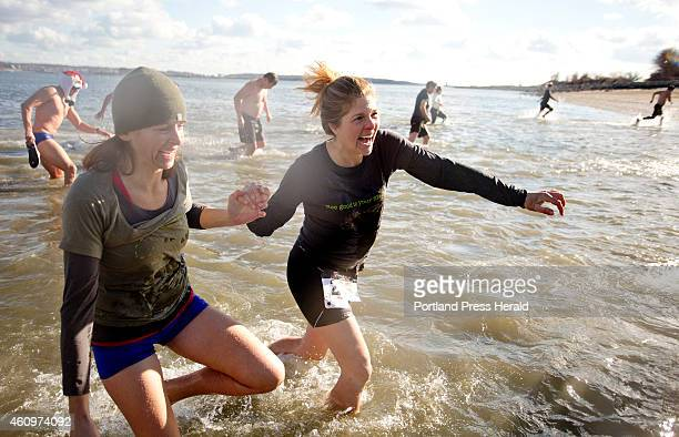 Tracy Weinrich at right runs out of the cold water with a friend after the duo participated in the Natural Resources Council of Maine's Polar Dip on...