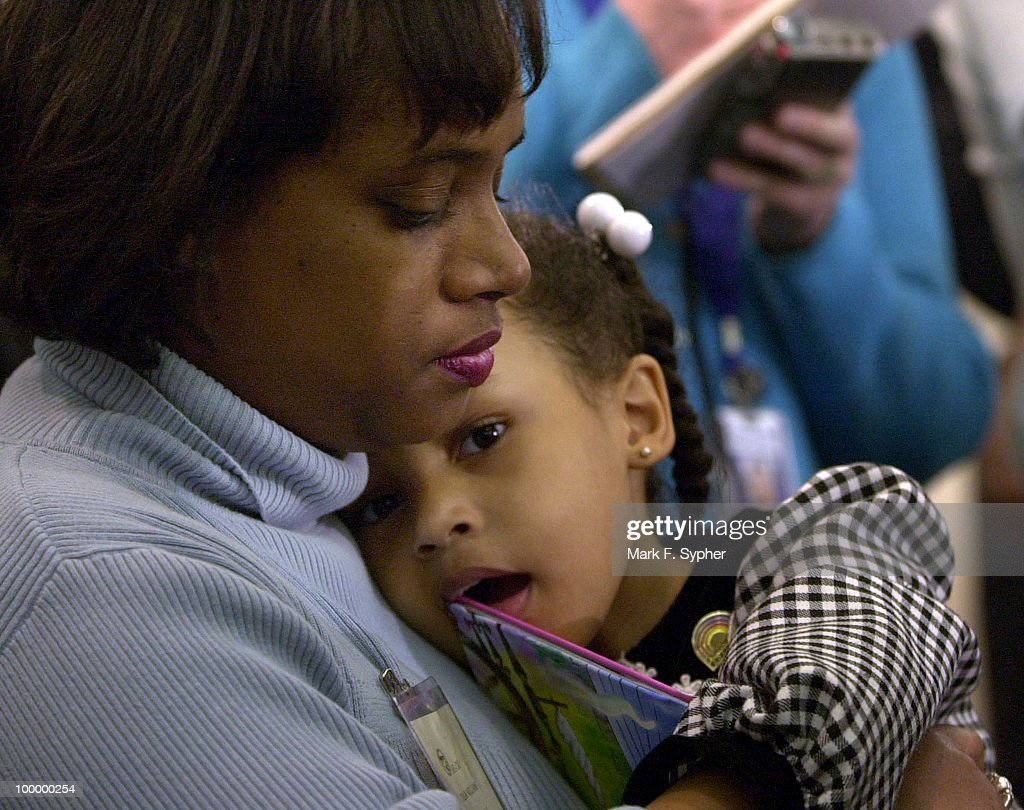 Tracy Williams holds her four year-old daughter, Taylor, duing a press conference in the U.S. Capitol that included about twenty-five ex-Enron employees who took a bus from Texas to meet with Congressional leaders. Tracy, a four year Enron employee, and her husband Daryl both worked for Enron before being laid off.