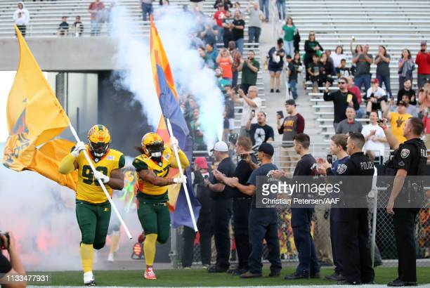 Tracy Sprinkle and Carl Bradford of the Arizona Hotshots carry the flag and lead their team on to the field for the Alliance of American Football...