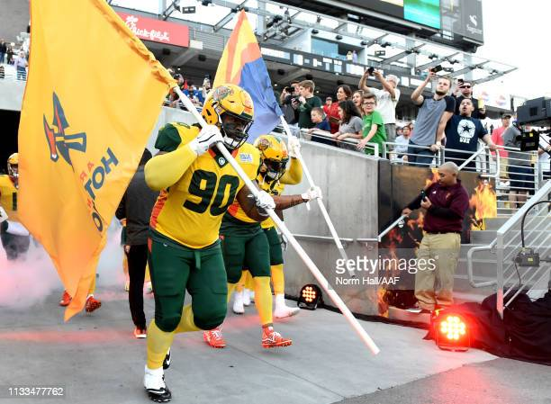 Tracy Sprinkle of the Arizona Hotshots carries the flag and leads his team on to the field for the Alliance of American Football game against the...