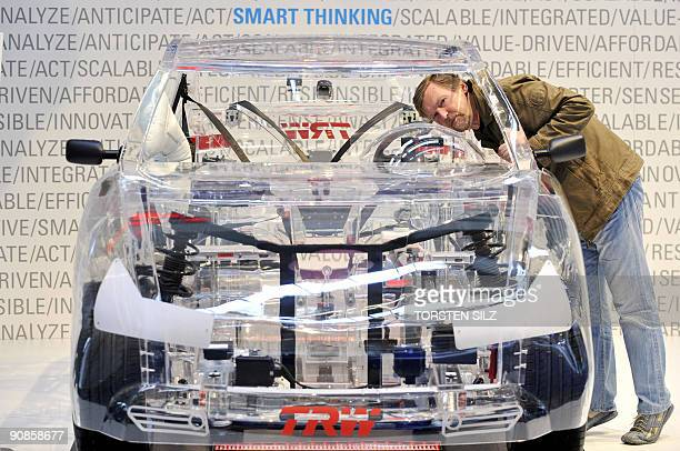 A trade fair visitor looks at a car with a transparent body at the stand of car parts manufacturer TRW during the 63rd International Motor Show in...