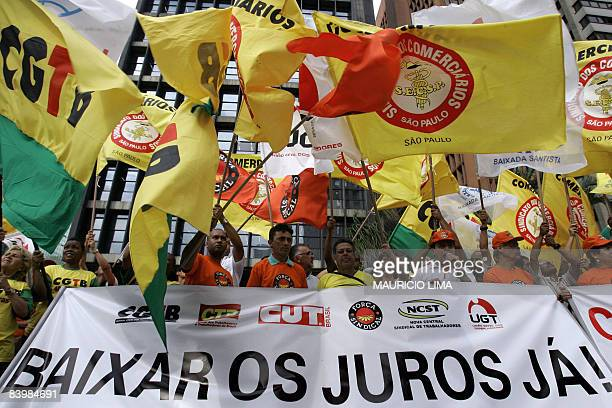 Trade union members flutter flags during a demonstration in front of Brazil's Central Bank building at the financial centre of Paulista Avenue in Sao...