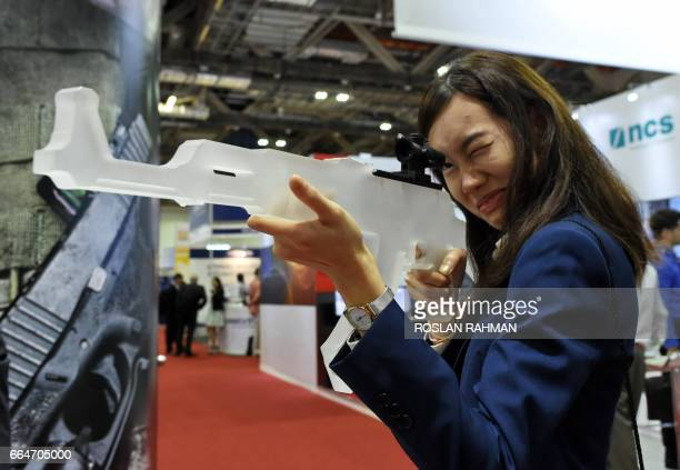 A trade visitors looks through a rifle scope at the display booth during the Milipol AsiaPacific conference and exibition of homeland security in...