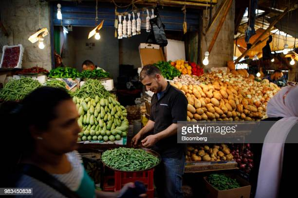 A trader arranges a display of okra at a local market in downtown Amman Jordan on Thursday June 21 2018 President Trump and First Lady Melania Trump...
