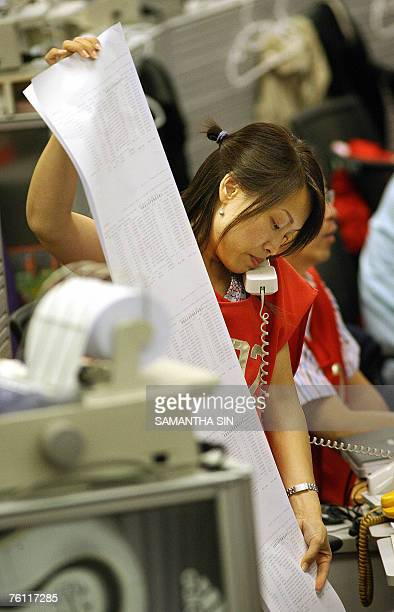 A trader at the Hong Kong Stock Exchange looks at her printout papers while on the phone during the trading day 16 August 2007 Hong Kong share prices...