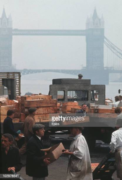 A trader balances goods on his head at Billingsgate fish market London circa 1970 In the background is Tower Bridge