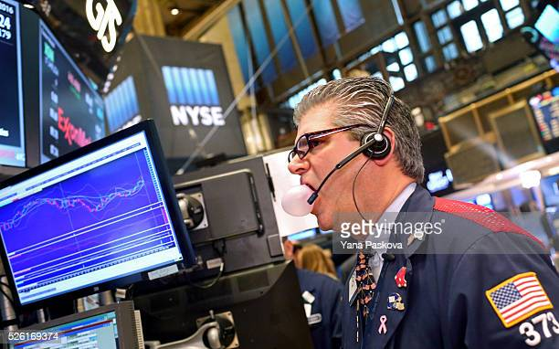 A trader blows out a chewing gum bubble while working on the floor of the New York Stock Exchange on April 29 2016 in New York City The Dow Jones...