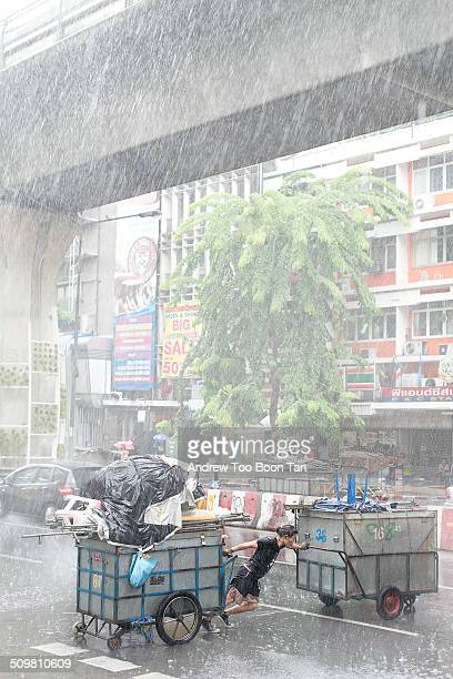 Trader braves the elements and road traffic to bring two containerloads of his merchandise to safety as a thunderstorm lashes Central Bangkok.