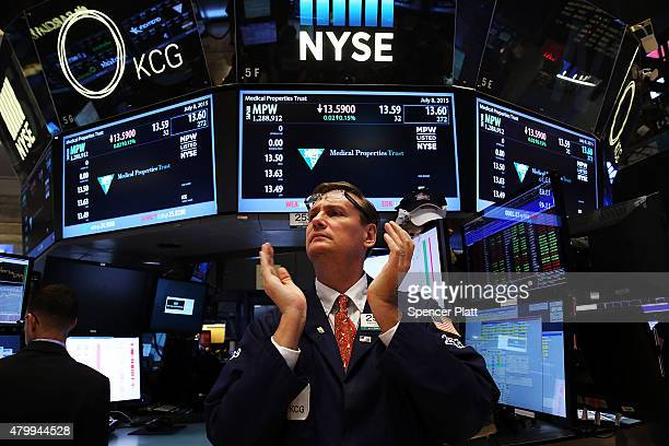 A trader claps on the floor of the New York Stock Exchange at the close of the day after trading was paused for nearly four hours due to a 'technical...