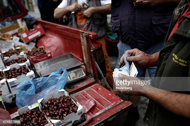 A trader counts euro banknotes as he sells cherries from the back of a pickup truck at a farmer's market on Kassandrou street in Thessaloniki Greece...