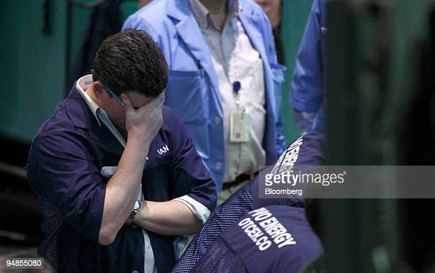 A trader covers his eyes while working in the crude oil options pit on the floor at the New York Mercantile Exchange in New York US on Tuesday April...