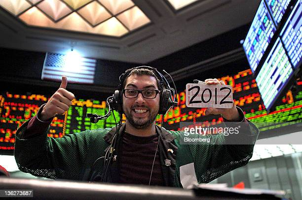 A trader displays a trading card with 2012 written on it for a photograph in the Eurodollar options pit at the CME Group's Chicago Board of Trade...