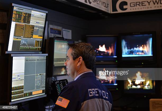 A trader from Greywolf watches prices as monitors in the background show videos of a fireplace on the floor of the New York Stock Exchange December...