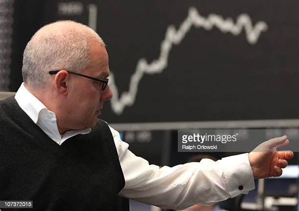 A trader gestures in front of the DAX Index board on the floor of Frankfurt stock exchange on December 7 2010 in Frankfurt am Main Germany The DAX...