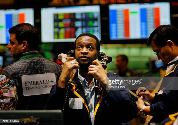 A trader handles multiple phones whilst dealing in metals and petroleum futures and options on the trading floor on the New York Mercantile Exchange...
