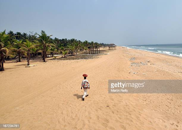 Trader heads along the long empty beach. The hawkers comes out with crafts to see the ex pats and tourists on Snake Island, a spit of land facing the...