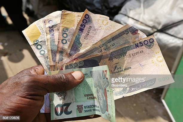 A trader holds 20 and 500 denomination naira banknotes at the Swali market in Yenagoa Nigeria on Thursday Jan 14 2016 With his security forces...