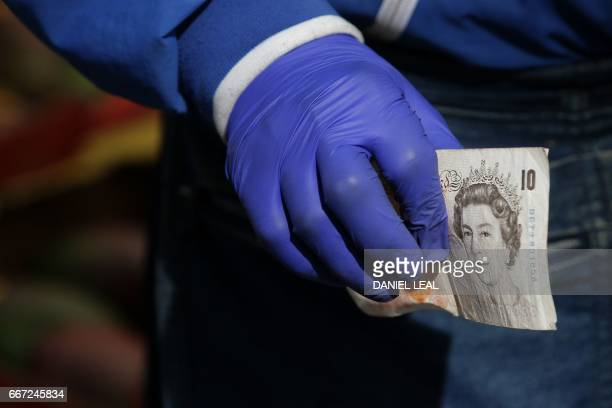 A trader holds a ten pound sterling note as a customer pays for goods at Whitechapel Market in east London on April 11 2017 Rising clothing and food...