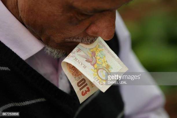 A trader holds a ten pound sterling note in his mouth as he prepares a customer's order at Whitechapel Market in east London on April 11 2017 Rising...