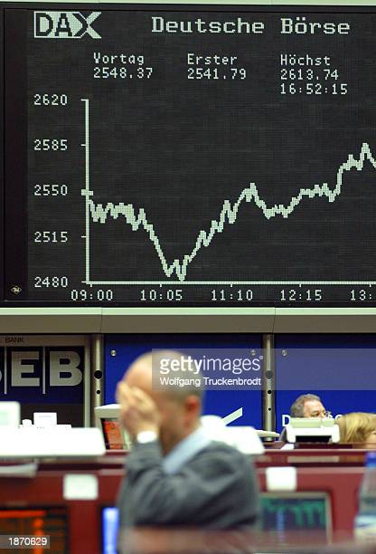 A trader holds his head as an electronic board shows the Dax index's sharp drop March 25 2003 in Frankfurt Germany The Dax dropped in morning trading...