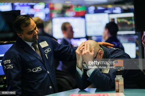 A trader is comforted by a coworker as they work on the floor of the New York Stock Exchange on March 1 2018 in New York City Major stock indexes...