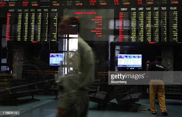 A trader is reflected against the trading hall of the Karachi Stock Exchange in Karachi Pakistan on Thursday June 16 2011 Karachi Stock Exchange...