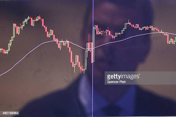 Trader is reflected in a market screen on the floor of the New York Stock Exchange on August 25, 2015 in New York City. Following a day of steep...