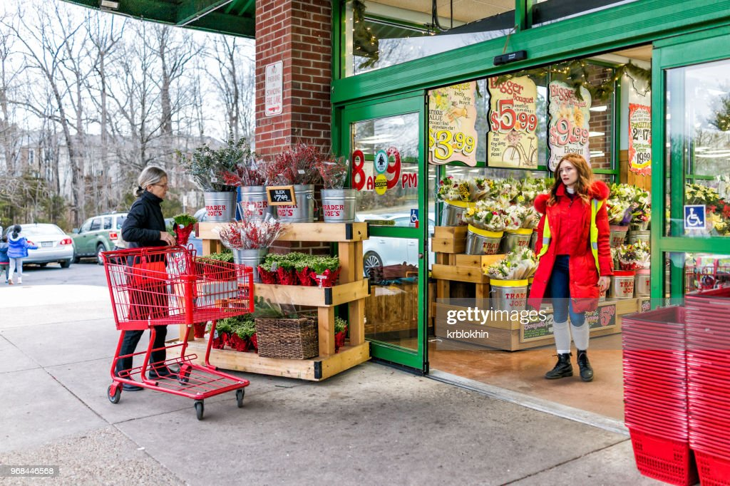 Trader Joe's employee in red clothes with customer, trolley shopping carts by store entrance doors outside women, winter flower pots, gardening plants in Virginia : Stock Photo